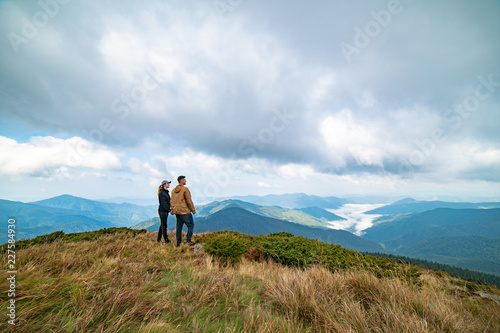 Photo  The happy man and a woman standing on the top of a mountain