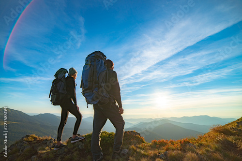 Fototapeta The couple standing on the mountain with a picturesque sunrise background obraz