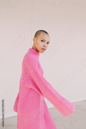 Girl in pink dress against white wall