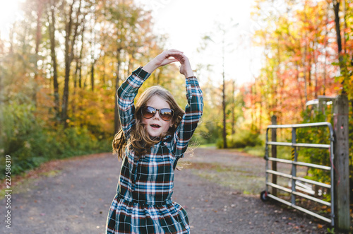 Happy girl in sunglasses twirling