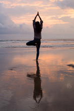 Woman Silhouette Yoga Practicing On The Beach