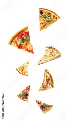 Set with falling different pizza slices on white background