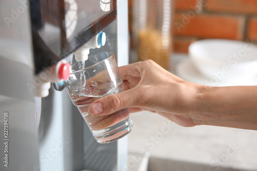 Woman filling glass with water from cooler indoors, closeup