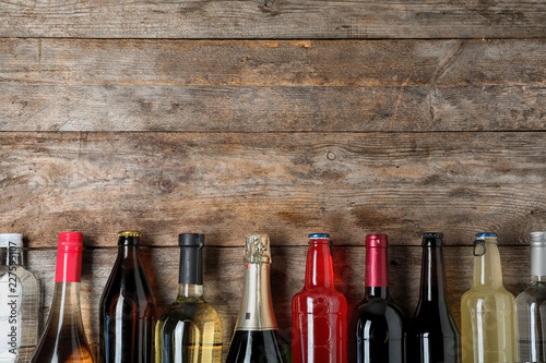 Bottles with different alcoholic drinks on wooden background, top view. Space for text
