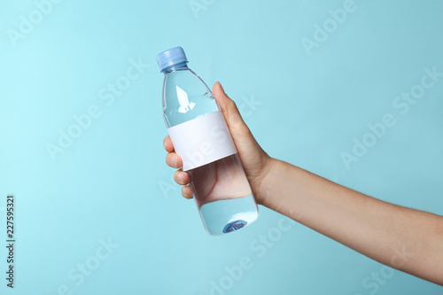 obraz PCV Woman holding plastic bottle of pure water with blank tag on color background