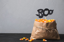 Paper Bag With Tasty Candy Corns On Table Against Gray Background. Space For Text