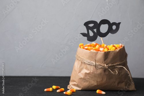 Fotografie, Obraz  Paper bag with tasty candy corns on table against gray background