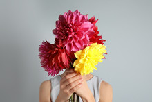 Woman Holding Bouquet Of Beautiful Dahlia Flowers Against Gray Background