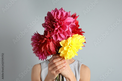 Stampa su Tela Woman holding bouquet of beautiful dahlia flowers against gray background