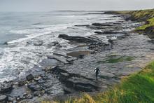 Surfer Walking On The Rocks Near The Sea