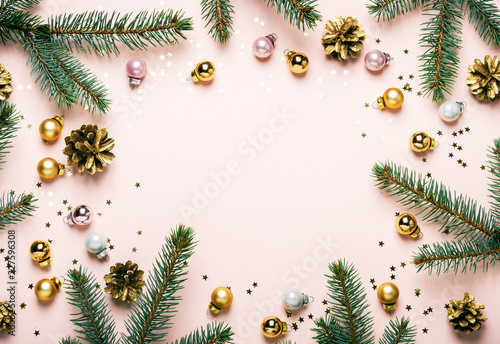 Pastel Pink Christmas Festive frame of fir branches, golden balls and confetti