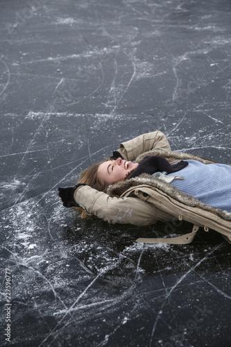 Fotobehang Wintersporten Enjoying woman lying on ice