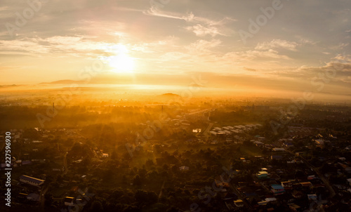 Aerial view of golden sunlight at sunrise with fog covered city town at the summer seasons.