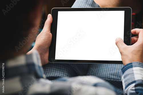 Stampa su Tela Mockup tablet image, Man using tablet computer while sitting relax on chair with