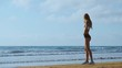 Girl's legs in sports clothes standing near the ocean and touching her hair in slow motion.