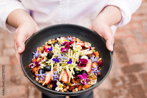 hands holding a bowl of granola