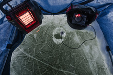Ice Fishing Inside A Small Portable Ice House.