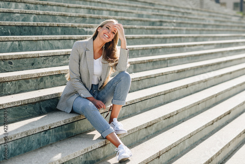Foto Beautiful young blonde woman smiling on urban steps.