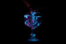 Stream Of Water Splashing Into A Full Glass Under Red And Blue Lights Isolated On A Black Background