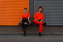 Beautiful Fashionable Young Stylish Couple In Fashion Orange Clothes With Caps Sit Near The Metal Gray And Orange Wall