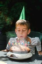 Boy With Green Hat Blowing Bir...