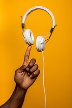 Concept Shot Of Black Man Doing Balance With White Headphones
