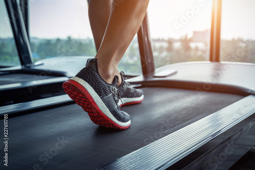 Obraz na płótnie Male feet in sneakers running on the treadmill at the gym