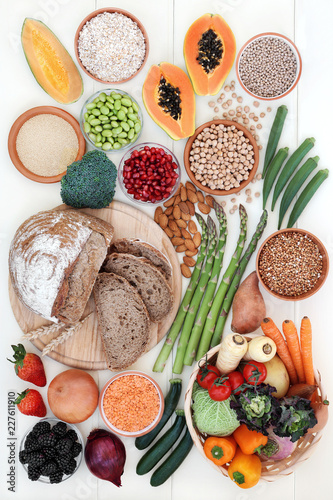 Poster Assortiment Healthy high fibre food concept with fruit, vegetables, whole grain rye bread, legumes, grains and cereal on rustic white wood background. High in antioxidants, anthocyanins, vitamins and minerals.