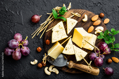 Cheese with grape and nuts on wooden board