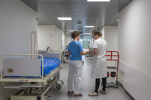 Two Nurses Talking In A Hallway