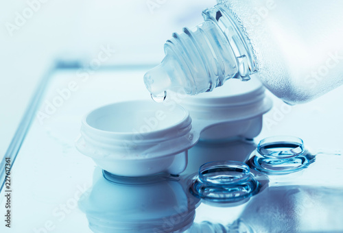 Bottle with lens solution and case on table #227617361