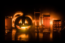 Glass Of Cold Light Beer With Pumpkin On A Wood Background For Halloween. Glass Of Fresh Beer And Pumpkin On A Dark Toned Foggy Background