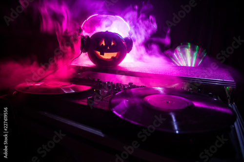 Halloween pumpkin on a dj table with headphones on dark background with copy space. Happy Halloween festival decorations and music concept - 227619556