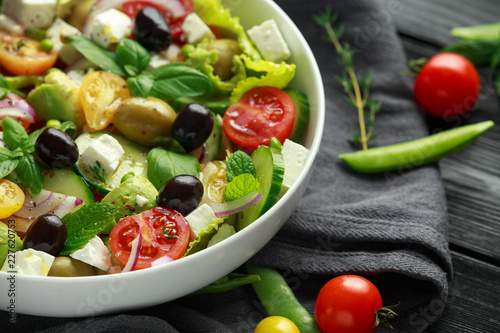 Healthy low calories salad with lettuce, heirloom tomatoes, avocado, feta cheese, red onion, cucumber, sweet peas, olives, thyme, mint and basil.