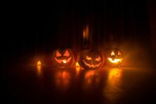 Halloween Pumpkin Head Jack O Lantern With Glowing Candles On Background. Pumpkins On Wooden Floor