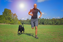 Man Running With His Dog On The Meadow.