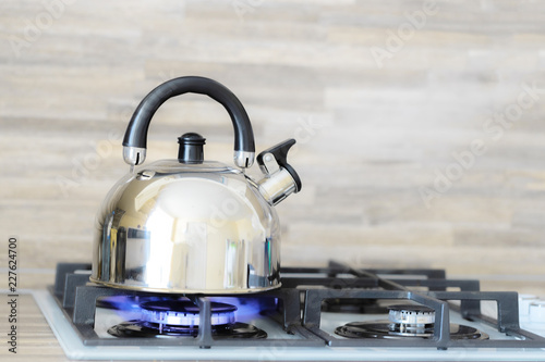 Fotografering  kettle on a gas stove flame burn not boiling
