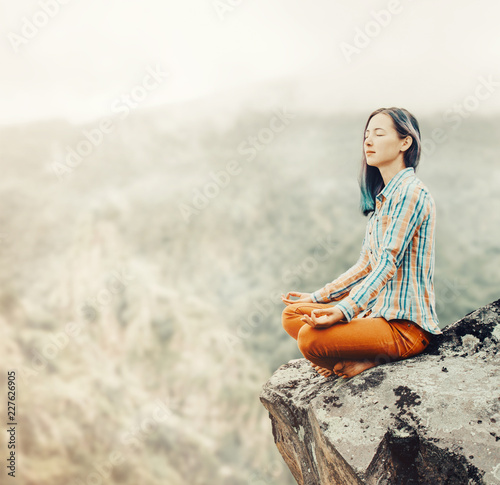 Traveler woman relaxing in pose of lotus in the mountains.