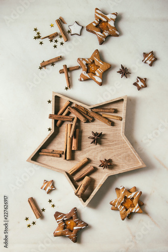 Homemade Christmas star shape sugar caramel cookies with frosting and orange citrus jam, cinnamon sticks and anise over white marble background. Flat lay, space. Sweet xmas or new year gift.
