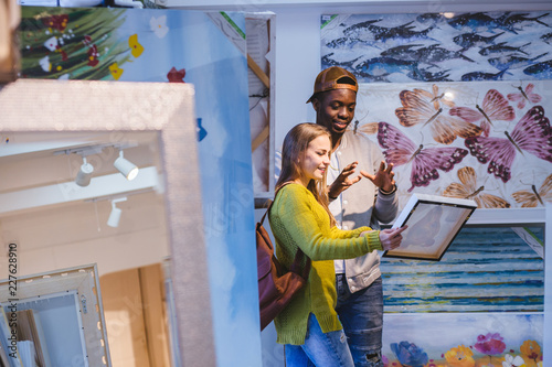 Fotomural  Young couple with different colour skins choosing a picture in art gallery or store