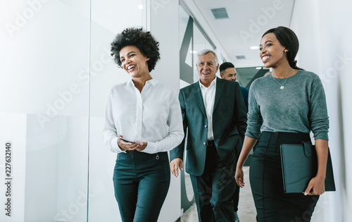 Team of corporate professionals in office corridor