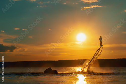 Silhouette of a fly board rider over a river against the setting sun.
