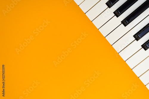 Abstract orange background with the piano keys in the up-right corner - 227633399
