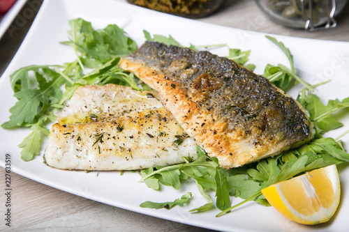 Photo Grilled seabass fillet with arugula and lemon. Close-up.