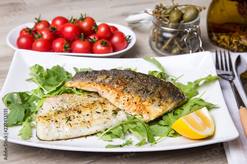 Fotografija Grilled seabass fillet with arugula, lemon, tomatoes and capers