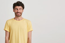 Clouse Up Of Afraid Fearful Young Man With Dark Brown Hair And Beard Wears Yellow Casual Tshirt, Look Right, Standing Left Side Isolated Over White Background