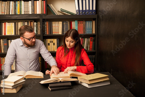 Fotografia  a man and a woman read books in the library are preparing for the exam