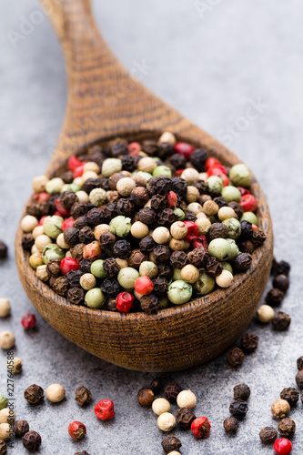In de dag Aromatische Peppercorn mix in a wooden bowl on grey table.