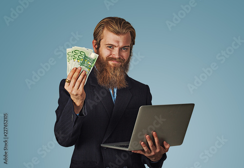 Fotografía  smiling man holding laptop and money euro bills cash