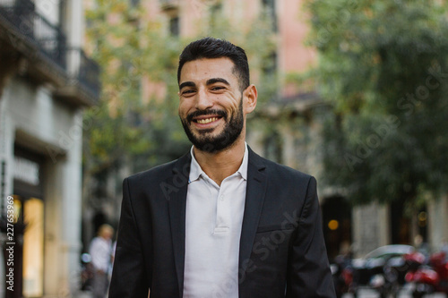 Fotomural Handsome arabic guy smiling. Successful man walking on the street